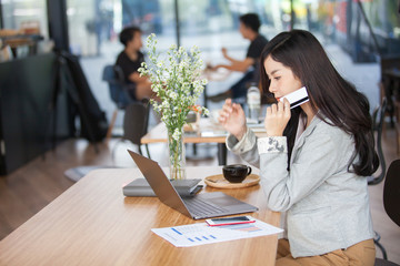 Young  Asia woman holding credit card and using laptop computer. Online shopping concept