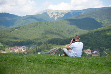 Man with camera sitting on a hill and photography nature. Summer day