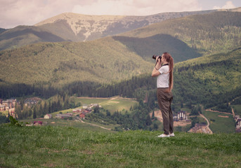 Girl with camera stands on a hill and photographing mountain. Forest on background