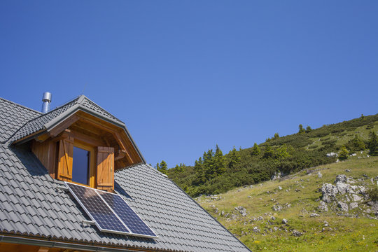 Mountain cottage with solar panels, against clear blue sky, space for text
