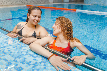 Two fit sporty women talking at the border of swimming pool