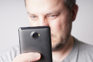 middle aged man looking at mobile smartphone or taking selfie. shallow depth of field