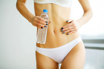 Health. Woman Holds a Bottle of Clean Water in the Hands. Female Stomach. Woman in White Underwear. Healthy Eating. Young Girl with the Perfect Shape. High Resolution