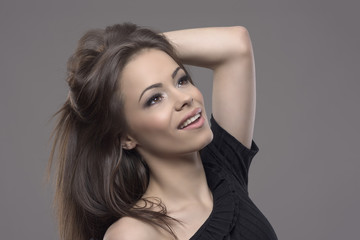 Portrait of beautiful young brunette woman holding healthy shiny brown hair and looking up over gray background.