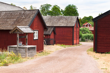 Vintage village well beside a gravel road and some barns. Homes in the background. Location Stensjo in Smaland, Sweden.