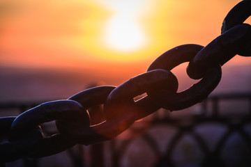 Metal chains of the fence against the background of the sunrise / sunset