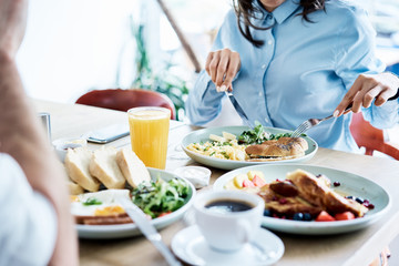 Couple having healthy breakfast in modern restaurant. People eating out together