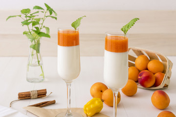 Glass of Panna Cotta, traditional sweet italian dessert, with apricot jelly and touch of yellow hot habanero chilli, cinnamon, decorated with fresh mint.