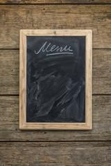 Restaurant menu chalkboard on rustic wooden wall