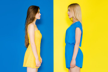 Female fashion models looking at each other isolated on blue and yellow background Wall mural