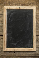 Blank chalkboard on rustic wooden background