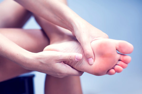 Woman hand holding foot with pain, health care and medical concept