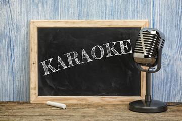 Karaoke written on vintage chalkboard with microphone