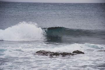 typical windy day in gran canaria, canary islands, spain. ideal for surfing, bigger waves in the sea, turquoise blue water in the ocean