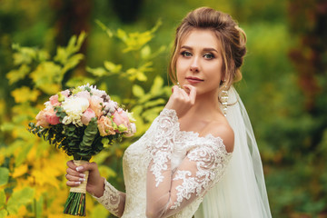 Portrait of the bride with bouquet in hands on the background of autumn forest