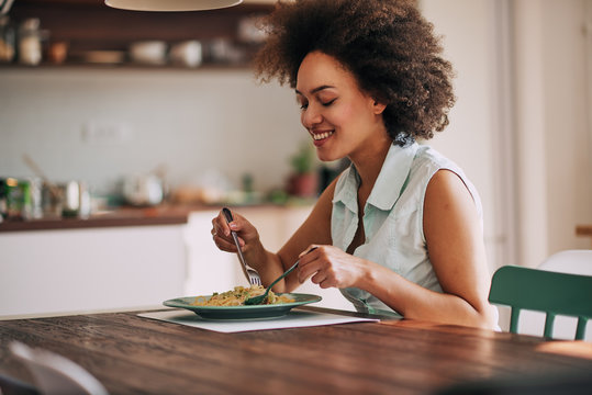 Beautiful mixed race woman eating pasta for dinner while sitting at kitchen table.