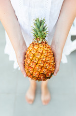 View of incognito female in white dress holding fresh and tasty pineapple in hands against wall background with palm leaf. Concept of fresh exotic fruits and raw summer food.