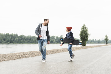 Happy father and son with skateboard at the riverside