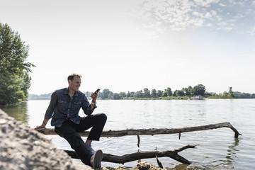 Mature man sitting at Rhine riverbank, using smartphone