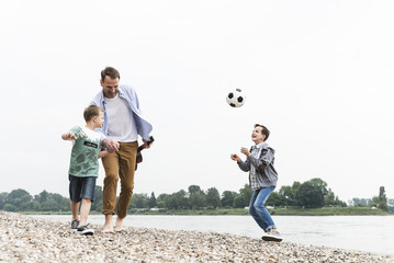 Happy father with two sons and football walking at the riverside