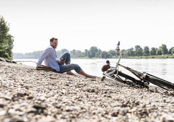 Mature man with bike and smartphone sitting at Rhine riverbank