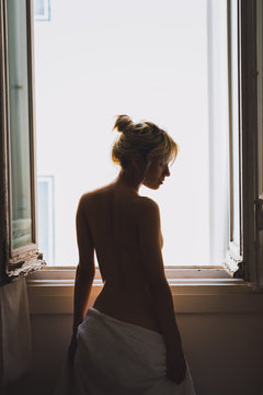 Topless young woman standing near window