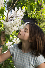 Portrait of girl smelling blossom of white lilac