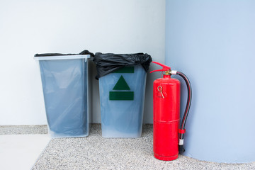 Fire extinguisher on floor beside plastic rubbish bin at building corner background