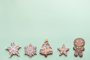 Row of five gingerbread cookies decorated with sugar icing on bright green background