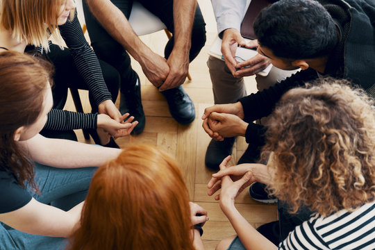 High angle of a group of teenagers sitting in a circle during group therapy for bullying victims