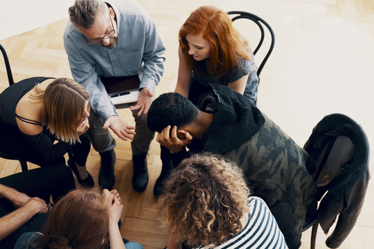 Top view of a group of difficult teenagers talking to a school counselor in detention