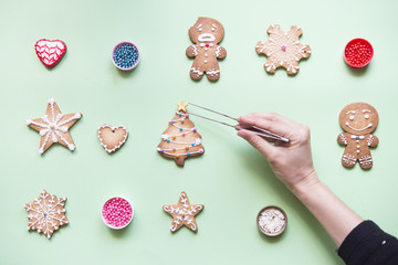 Woman's hand decorating Gingerbread cookies