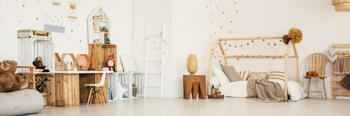 Panoramic photo of a child's bedroom interior with wooden furniture, house bed, stool and wall stickers