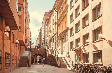 Archway and historical houses with pedestrian of old swedish city