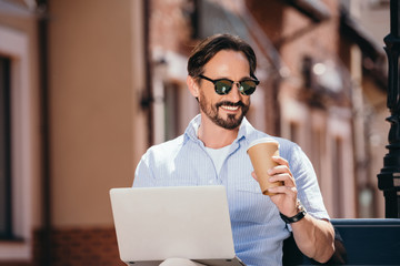 handsome smiling man sitting on bench with laptop and coffee in paper cup