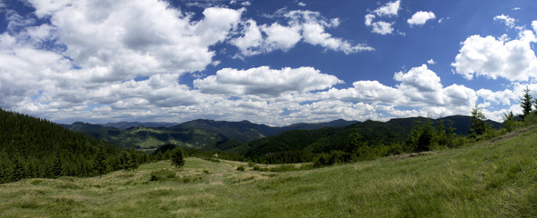 Paniramic view of mountain landscape in the summer under beautiful cloudy sky. Ukraine, Carpathians, Dzembronia village.