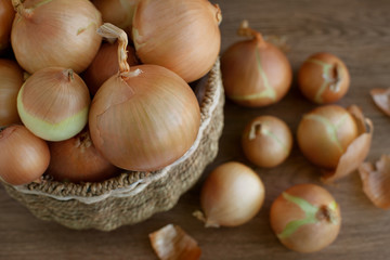 Onions are seen from above. Onions in a wicker basket and next to it. View from above. A large head of onions. A lot of onions are scattered on the table. Vegetables for a healthy diet.