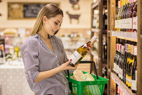 Portrait of happy blonde woman choosing wine while standing inside big grocery shop. Beautiful girl holding and looking or reading wine bottle with blank copy space while doing shopping in supermarket