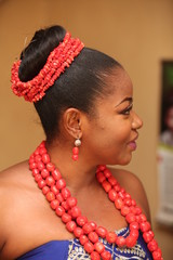 An african female of the Igbo tribe in Nigeria dressed up for her traditional marriage rites poses for pictures. She is dressed in head wrappers, beaded dress and beads.