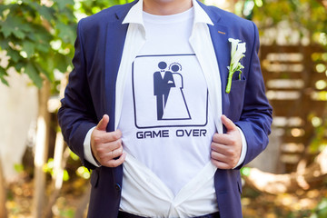 newlywed in blue costume with opened shirt showing t-shirt with funny picture of marrieds