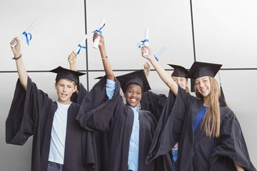 Composite image of portrait of smiling students holding degree
