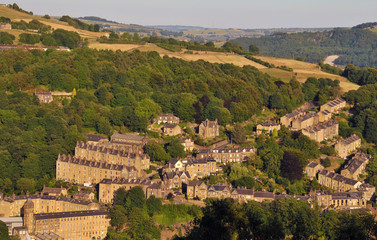 an aerial view of the town of hebden bridge in summer with hillside sloping streets of stone house surrounded by green woodland and west yorkshire fields and farms