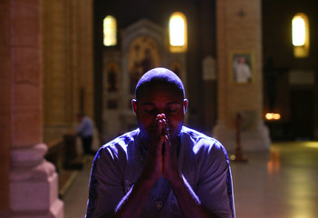 Nigerian Charles Otokiti, 37, who was rescued at sea after passing through Libya in 2016, prays in a church in Rome