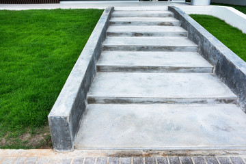 Concrete staircase at slope way beside grass field background