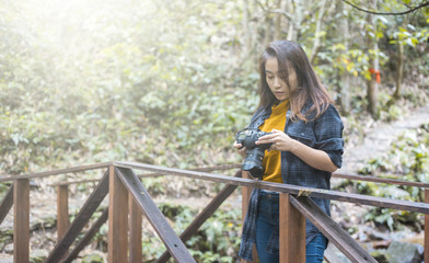 Photography and travel The girl holding the camera in humid forest zone.