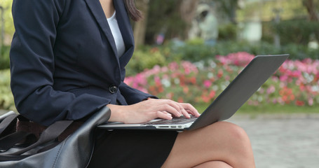 Businesswoman type on laptop computer at outdoor