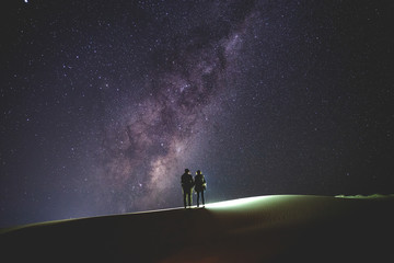 Landscape with Milky Way. Night sky with stars and silhouette of a standing  couple on sand hill.