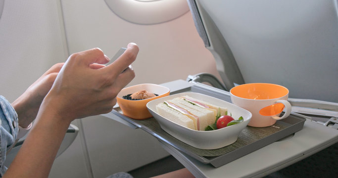 Woman taking photo on her flight meal on plane