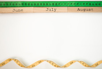 Three summer month - June, July and August - on wooden blocks with centimeter tape isolated on white. Summer calendar concept