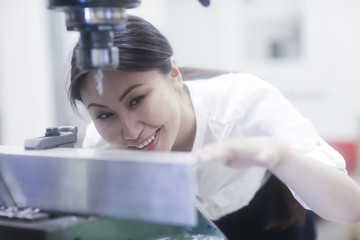 Smiling Female engineer preparing to drill a hole in a metal rail